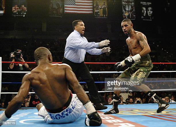 Diego Corrales watches as referee Tony Weeks steps in after Corrales knocked down Joel Casamayor in an IBF Junior Lightweight title elimination bout...