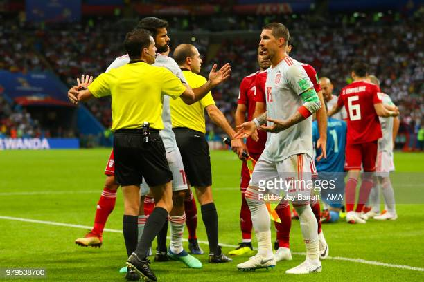 Diego Costa and Sergio Ramos of Spain exchange words with Referee Andres Cunha during the 2018 FIFA World Cup Russia group B match between Iran and...