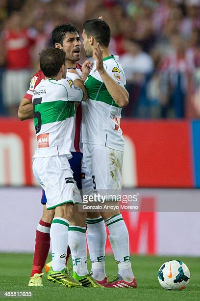 Diego Costa of Atletico de Madrid argues with Alberto Rivera of Elche FC and his teammate Alberto Tomas Botia during the La Liga match between Club...