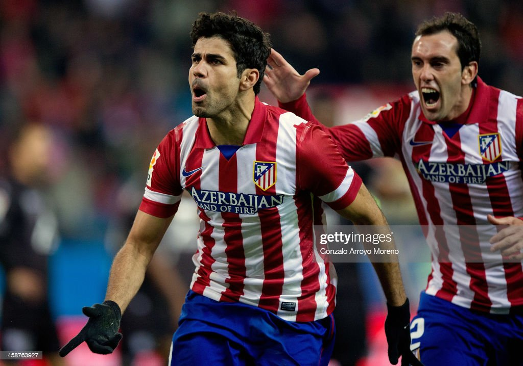 Diego Costa (L) of Atletico de Madrid celebrates scoring their second goal with team-mate Diego Godin (R) during the La Liga match between Club Atletico de Madrid and Levante UD at Vicente Calderon Stadium on December 21, 2013 in Madrid, Spain.