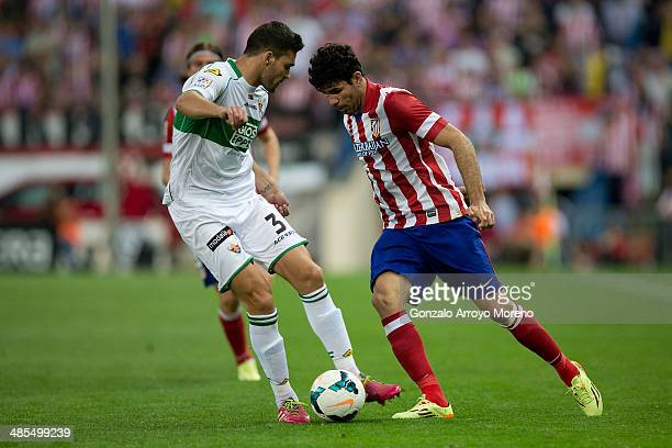 Diego Costa of Atletico de Madrid competes for the ball with Alberto Tomas Botia of Elche FC during the La Liga match between Club Atletico de Madrid...