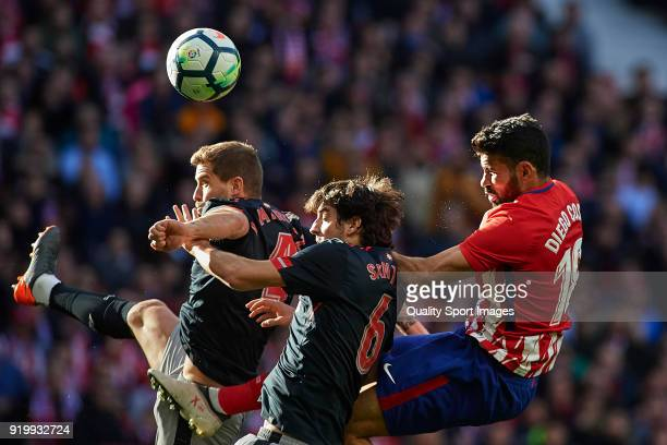 Diego Costa of Atletico de Madrid competes for the ball with Inigo Martinez and Mikel San Jose of Athletic Club during the La Liga match between...