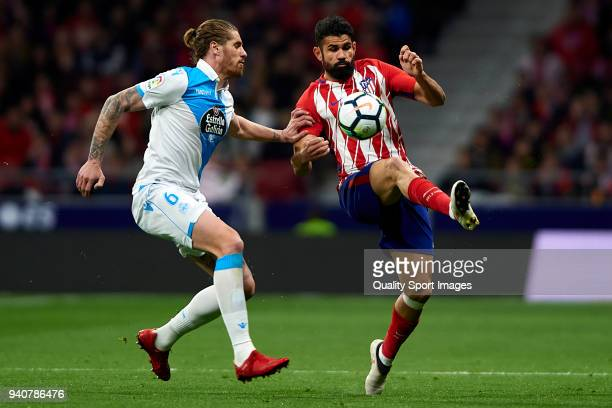 Diego Costa of Atletico de Madrid competes for the ball with Raul Albentosa of Deportivo La Coruna during the La Liga match between Atletico Madrid...