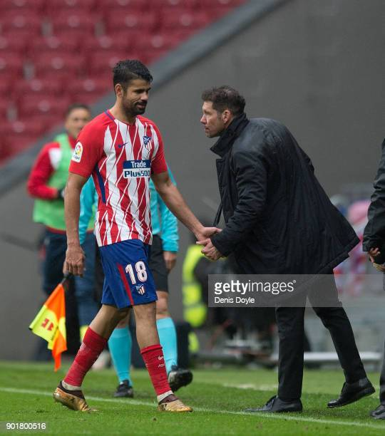 Diego Costa of Atletico Madrid shakes hands with Manager Diego Simeone of Atletico de Madrid after he was sent off during the La Liga match between...
