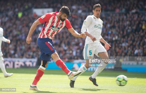 Diego Costa of Atletico Madrid shoots past Rafael Varane of Real Madrid during the La Liga match between Real Madrid and Atletico Madrid at Estadio...
