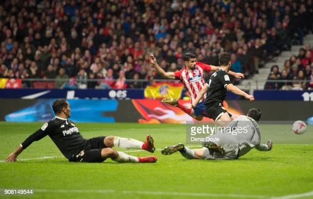 Diego Costa of Atletico Madrid shoots past Sergio Rico of Sevilla during the Copa del Rey Quarter Final First Leg match between Atletico de Madrid...