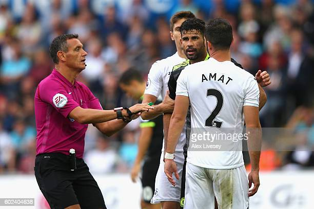 Diego Costa of Chelsea and Jordi Amat of Swansea City clash as referee Andre Marriner intervenes during the Premier League match between Swansea City...