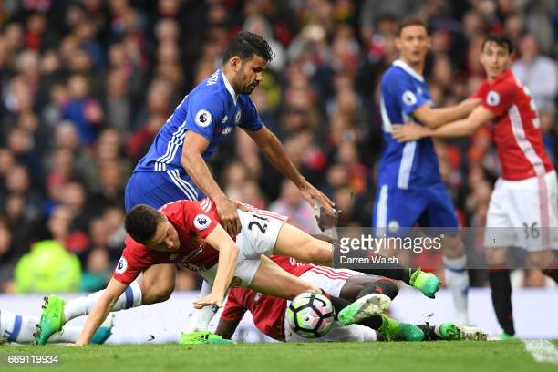 Diego Costa of Chelsea Ander Herrera of Manchester United and Eric Bailly of Manchester United colide during the Premier League match between...