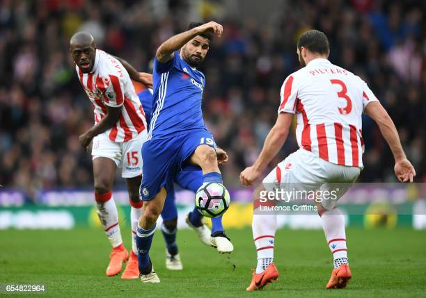 Diego Costa of Chelsea attempts to control the ball while under pressure from Bruno Martins Indi of Stoke City and Erik Pieters of Stoke City during...