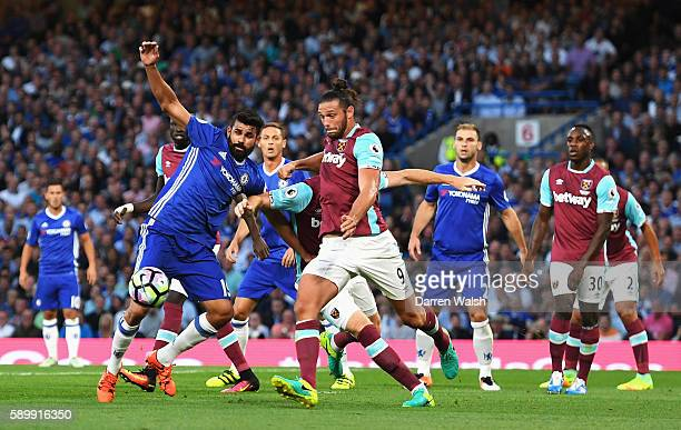 Diego Costa of Chelsea challenges for the ball with Andy Carroll of West Ham United during the Premier League match between Chelsea and West Ham...