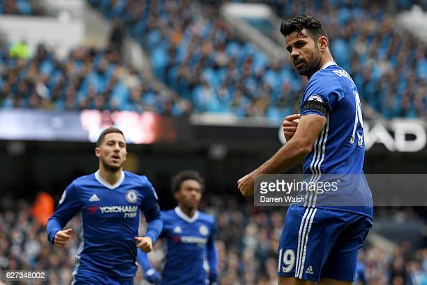 Diego Costa of Chelsea points his black armband to commemorate the victims of the plane crash involving the Brazilian club Chapecoense after scoring...
