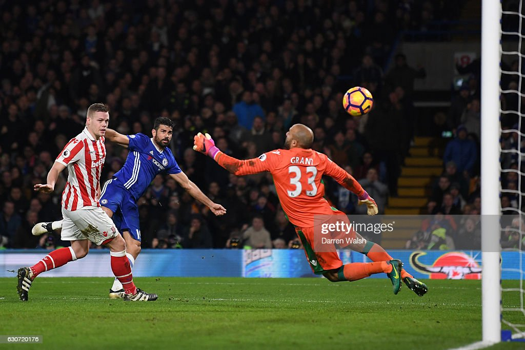 Diego Costa (2nd L) of Chelsea scores his side's fourth goal past Lee Grant of Stoke City during the Premier League match between Chelsea and Stoke City at Stamford Bridge on December 31, 2016 in London, England.