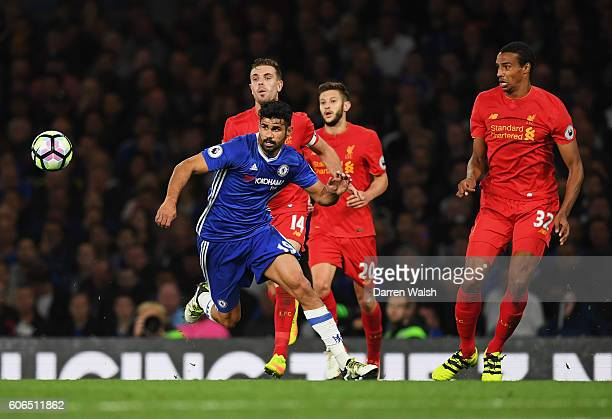 Diego Costa of Chelsea watches the ball with Jordan Henderson and Joel Matip of Liverpool during the Premier League match between Chelsea and...