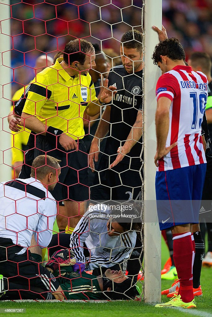 Diego Costa of Club Atletico de Madrid and Gary Cahill of Chelsea look on as Petr Cech of Chelsea receives treatment during the UEFA Champions League Semi Final first leg match between Club Atletico de Madrid and Chelsea at Vicente Calderon Stadium on April 22, 2014 in Madrid, Spain.