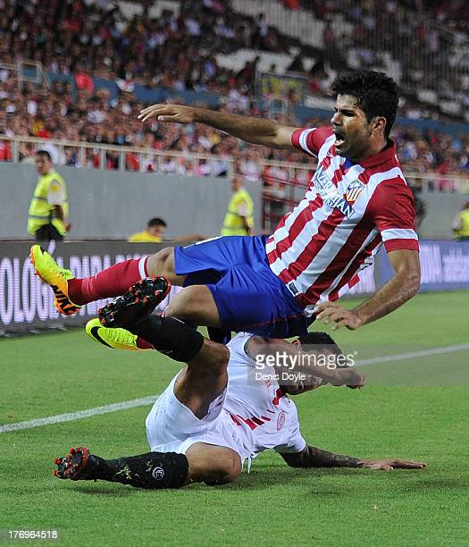 Diego Costa of Club Atletico de Madrid is tackled by Victor Machin 'Vitolo' of Sevilla FC during the La Liga match between Sevilla FC and Club...