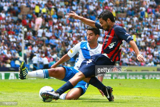 Diego de Buen of Puebla struggles for the ball with Walter Erviti of Atlante during a match between Puebla and Atlas as part of the Apertura 2013...