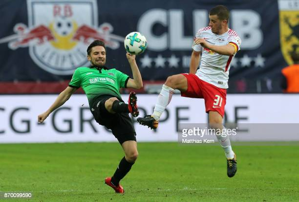 Diego Demme of Leipzig battles for the ball with Julian Korb of Hannover during the Bundesliga match between RB Leipzig and Hannover 96 at Red Bull...