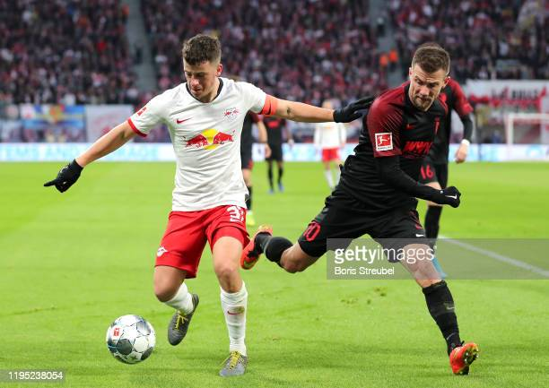 Diego Demme of RB Leipzig battles for possession with Daniel Baier of FC Augsburg during the Bundesliga match between RB Leipzig and FC Augsburg at...