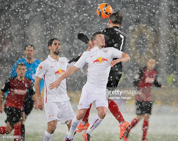 Diego Demme of RB Leipzig jumps for a header with Florian Niederlechner of Freiburg during the Second Bundesliga match between SC Freiburg and RB...