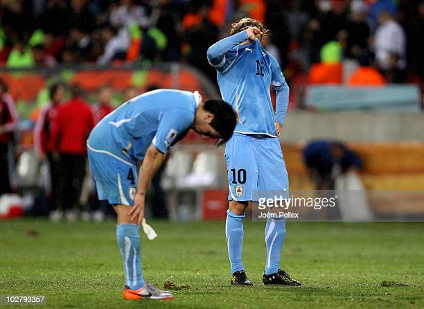 Diego Forlan and Jorge Fucile of Uruguay show their dejection after losing the 2010 FIFA World Cup South Africa Third Place Playoff match between...