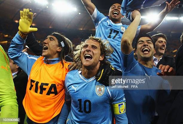 Diego Forlan Egidio Arevalo Luis Suarez of Uruguay and team mates celebrate winning the penalty shoot out and progress to the semi finals during the...