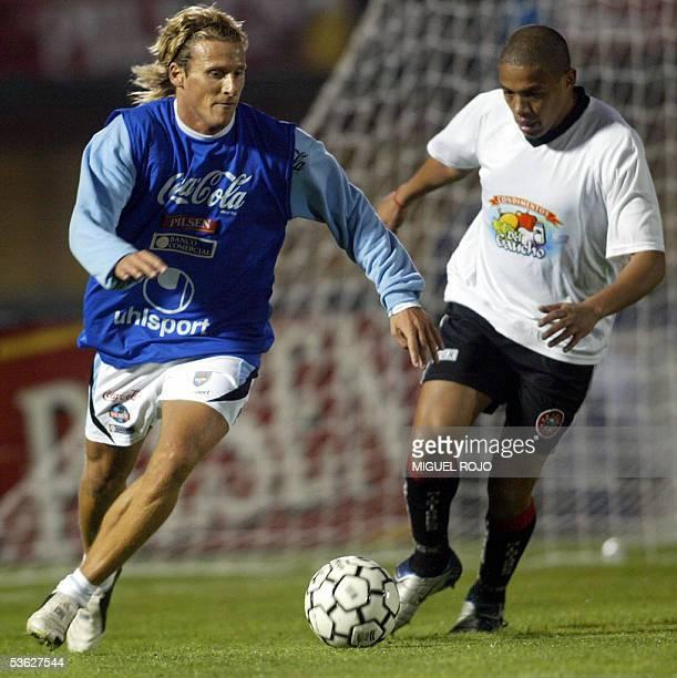 Diego Forlan elude la marca de un jugador no identificado de un club local durante una practica del seleccionado uruguayo el 31 de agosto de 2005 en...