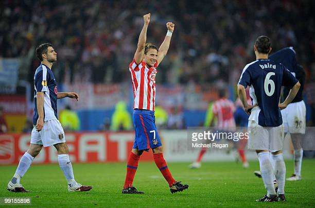 Diego Forlan of Atletico Madrid celebrates his victory while Chris Baird of Fulham looks dejected after the UEFA Europa League final match between...