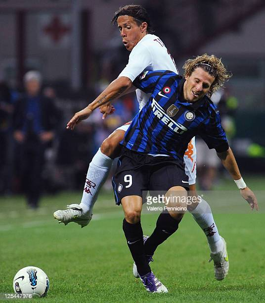 Diego Forlan of FC Internazionale Milano is challenged by Rodrigo Taddei of AS Roma during the Serie A match between FC Internazionale Milano and AS...