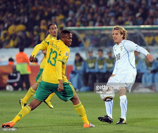 Diego Forlan of Uruguay and Kagisho Dikgacoi of South Africa compete during the 2010 FIFA World Cup Group A match between South Africa and Uruguay...