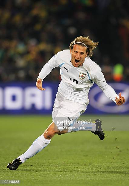 Diego Forlan of Uruguay celebrates after scoring the opening goal during the 2010 FIFA World Cup South Africa Group A match between South Africa and...