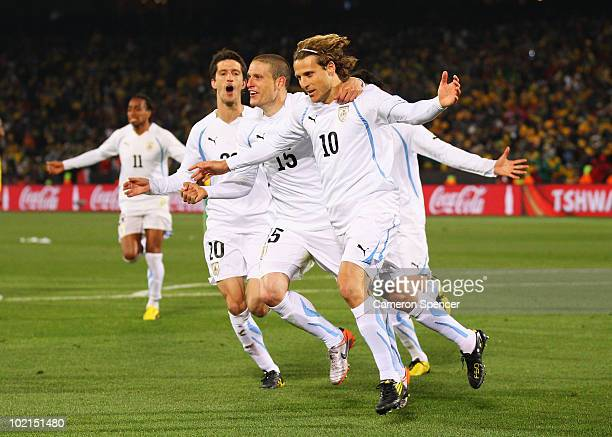 Diego Forlan of Uruguay celebrates after scoring the second goal from the penalty spot with team mates Alvaro Fernandez and Diego Perez during the...
