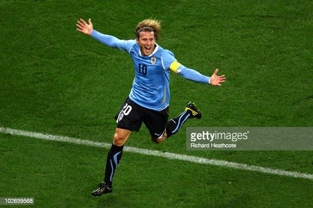 Diego Forlan of Uruguay celebrates scoring his side's first goal during the 2010 FIFA World Cup South Africa Semi Final match between Uruguay and the...