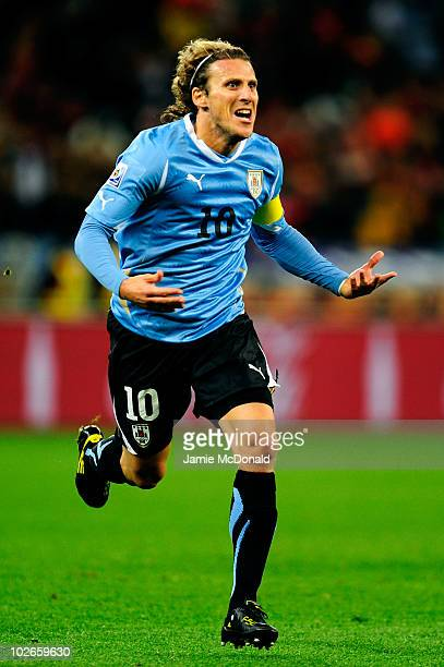 Diego Forlan of Uruguay celebrates scoring his team's first goal during the 2010 FIFA World Cup South Africa Semi Final match between Uruguay and the...
