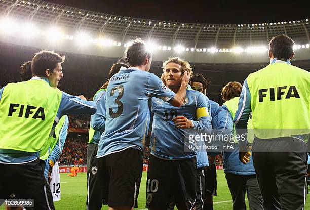 Diego Forlan of Uruguay celebrates scoring the equalising goal with teammate Diego Godin during the 2010 FIFA World Cup South Africa Semi Final match...