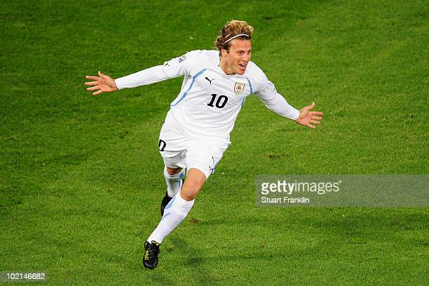 Diego Forlan of Uruguay celebrates scoring the opening goal during the 2010 FIFA World Cup South Africa Group A match between South Africa and...
