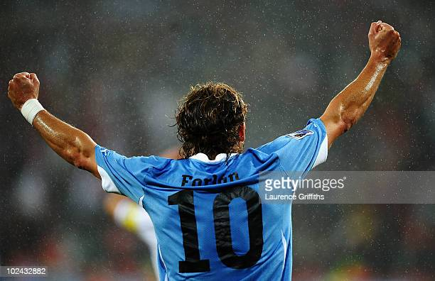 Diego Forlan of Uruguay celebrates team mate Luis Suarez scoring his second goal during the 2010 FIFA World Cup South Africa Round of Sixteen match...