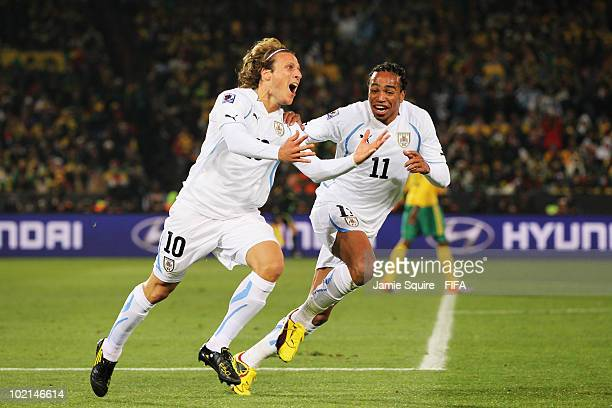 Diego Forlan of Uruguay celebrates with team mate Alvaro Pereira after scoring the opening goal during the 2010 FIFA World Cup South Africa Group A...