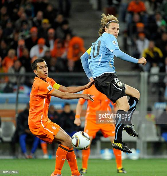 Diego Forlan of Uruguay eyes the ball with Giovanni van Bronckhorst of the Netherlands during the 2010 FIFA World Cup South Africa Semi Final match...