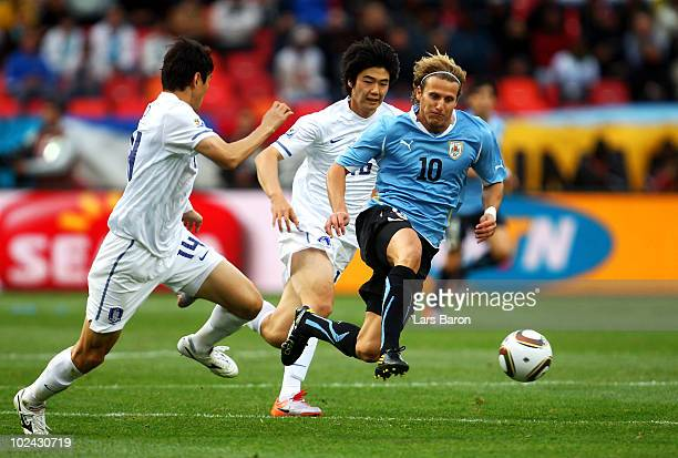 Diego Forlan of Uruguay is challenged by Lee Jung-Soo of South Korea during the 2010 FIFA World Cup South Africa Round of Sixteen match between...