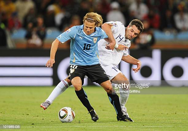 Diego Forlan of Uruguay is tackled by Jeremy Toulalan of France during the 2010 FIFA World Cup South Africa Group A match between Uruguay and France...