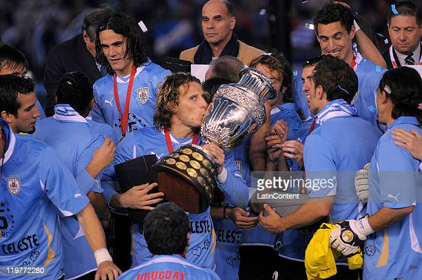 Diego Forlan of Uruguay kisses the trophy celebrating with teammates the victory of the Copa America 2011 against Paraguay at Antonio Vespucio...
