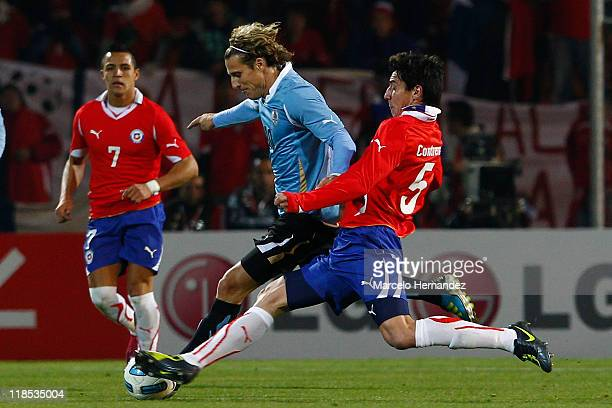 Diego Forlan of Uruguay struggles for the ball with Pablo Contreras of Chile during a match as part of group C of 2011 Copa America at Malvinas...