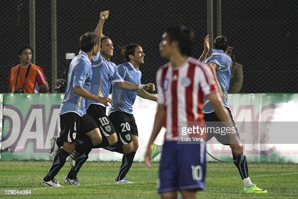 Diego Forlan Sebastian Eguren and Alvaro Gonzalez of Uruguay celebrates a scored in action during as part of the first round of the South American...