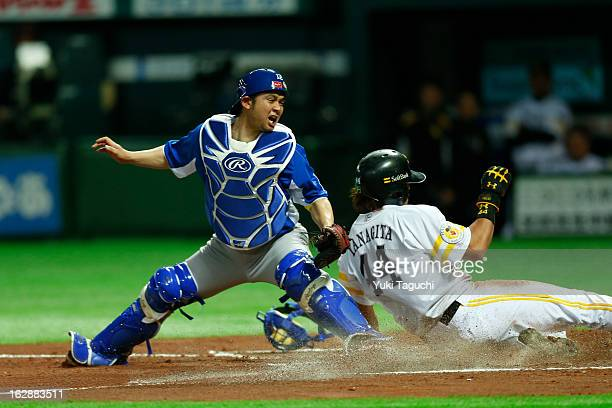 Diego Franca of Team Brazil attempts to block the plate as Yuki Yanagita of the SouthBank Hawks scores a run during the World Baseball Classic...