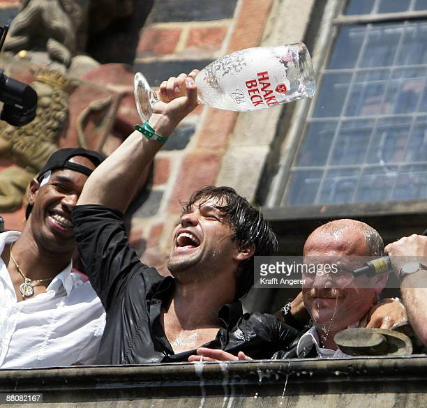 Diego gives head coach Thomas Schaaf of Werder Bremen a beer shower on the balcony of Bremen's town hall on May 31 2009 in Bremen Germany