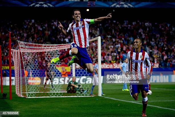 Diego Godin jumps to celebrate scoring their fourth goal close to his team mate Joao Miranda during the UEFA Champions League group A match between...