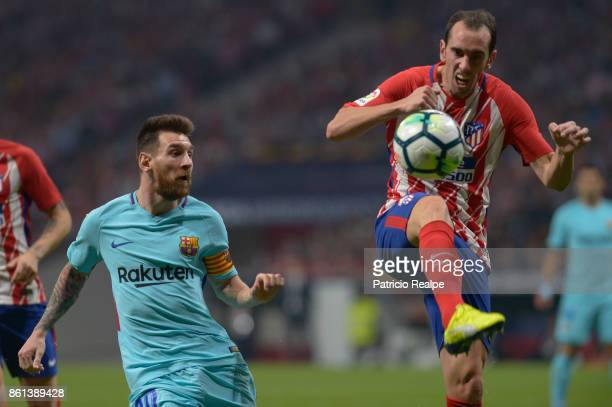 Diego Godin of Atletico de Madrid fights the ball with Lionel Messi of Barcelona during a match between Atletico Madrid and Barcelona as part of La...