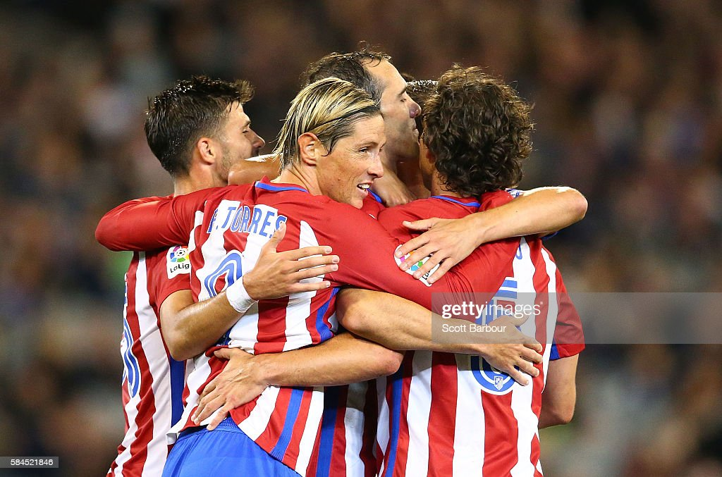 Diego Godin of Atletico de Madrid is congratulated by Fernando Torres and his teammates after scoring their first goal during 2016 International Champions Cup Australia match between Tottenham Hotspur and Atletico de Madrid at the Melbourne Cricket Ground on July 29, 2016 in Melbourne, Australia.