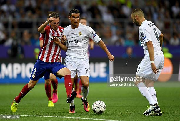 Diego Godin of Atletico Madrid is challenged by Cristiano Ronaldo of Real Madrid and Karim Benzema of Real Madrid during the UEFA Champions League...