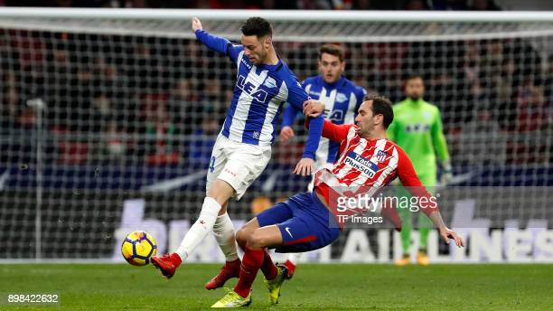 Diego Godin of Madrid and Burgui of Alaves battle for the ball during the La Liga match between Atletico Madrid and Deportivo Alaves at Wanda...